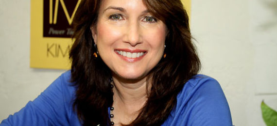 A picture of Kimberly Jentzen with brown hair falling over her shoulders, smiling at the camera. Her blue blouse picks up the green in her hazel eyes.