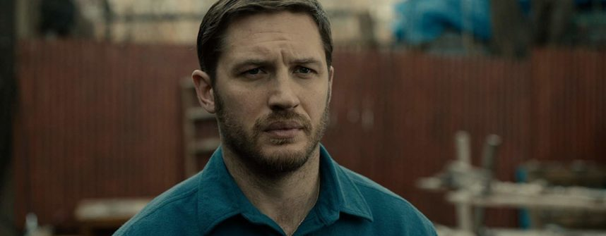 A picture of Tom Hardy in a blue button down shirt with a trimmed beard, standing outside.