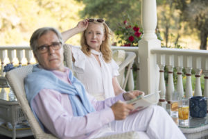 "A picture of Adora and Alan from ""Sharp Objects"" sitting on their white veranda during summer, with red roses in the background."
