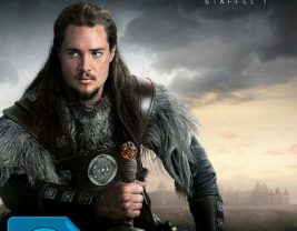 A picture of Alexander Dreymon dressed as a Viking and holding his sword with the horizon as the background.