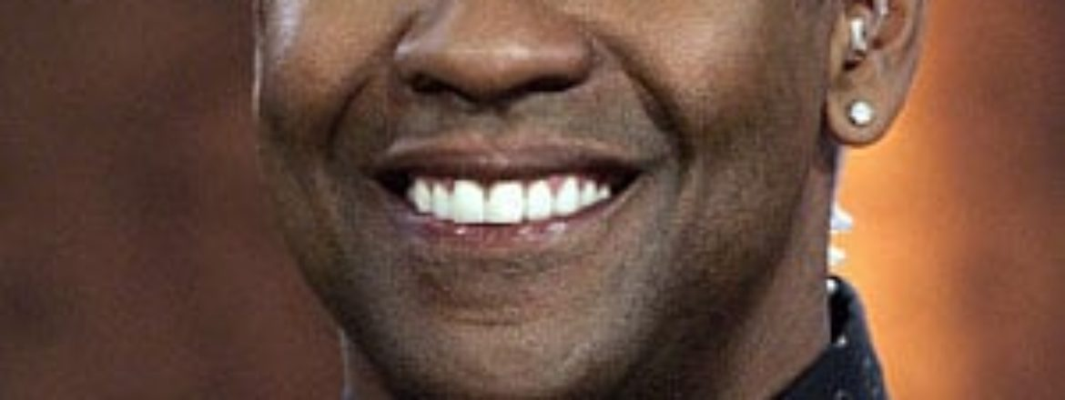 A picture of Denzel Washington smiling, wearing a black Oxford shirt with white buttons.