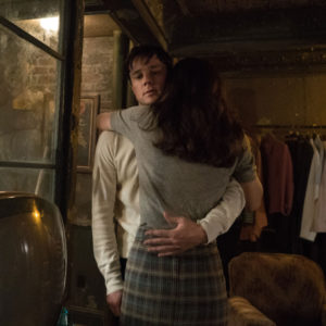 """A picture from the show """"The Man in the High Castle"""" of Frank and Julianna hugging in their dingy apartment."""