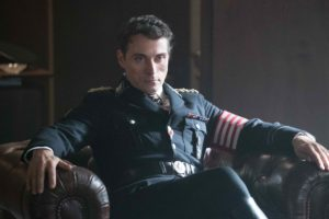"""A picture of actor Rufus Sewell playing Obergruppenführer John Smith in """"The Man..."""". He's looking menacing with his jet black hair and dark eyes, as he sits in his office wearing a Nazi uniform."""