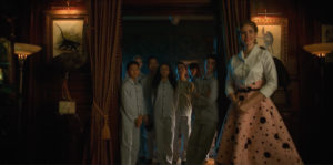 A picture of the Umbrella Academy kids dressed in their PJ's in the doorway of their father's den.