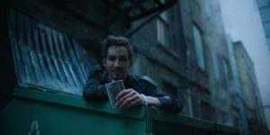 A picture of Robert Sheehan standing in a dumpster holding a flask.