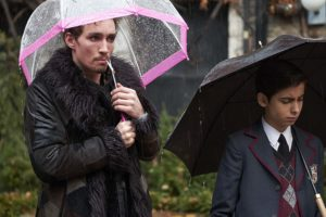 "A picture of two of the actors from ""The Umbrella Academy"" standing in the rain dressed in black for their father's funeral"