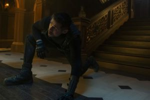 A picture of a man in black leather holding a knife and crouching at the bottom of some stairs.