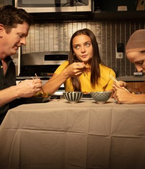 A picture of two adults and a teenaged girl sitting at the dinner table eating.