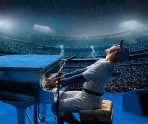 Elton John sits at his piano dressed in a sequened baseball uniform, playing to a huge crowd.