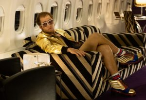 Elton John sits on a private airplane in a gold lame jumpsuit .