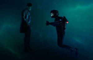The figures of a man in street clothes and one in a space suit stand suspended in a dark blue haze.