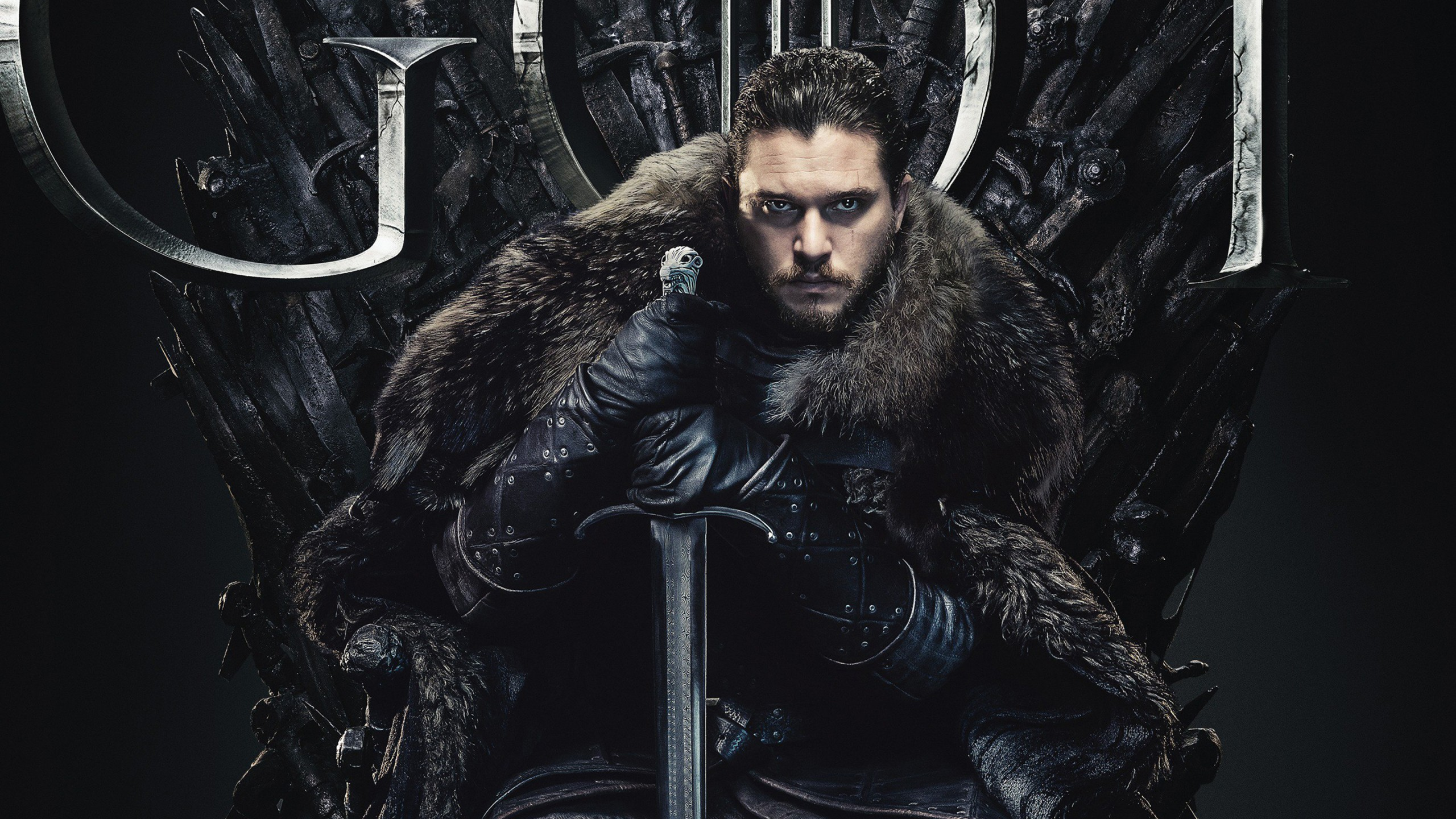 A picture of actor Kit Harrington playing Jon Snow in Game of Thrones, he sits on the throne of swords clad in leather and fur holding a sword and staring at the camera with a stealy look in his dark eyes.