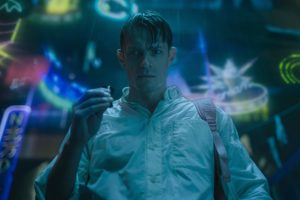 Actor Joel Kinnaman is standing in a dark neon lighted background in a white button down shirt, short brown hair and a muscular build.