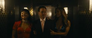 Jenifer Lopez and Constance Woo escort a well dressed businessman into a dark club.
