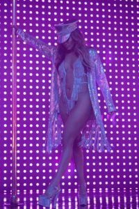 JLo standing on a lighted stage in a skimpy silver costume.