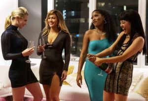 Four beautiful women stand in a high end apartment drinking champaign.