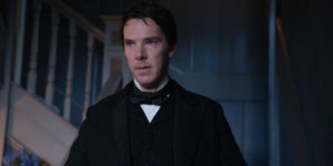 Actor Benedict Cumberland stands dressed in a black suit with bow tie, playing Thomas Edison.