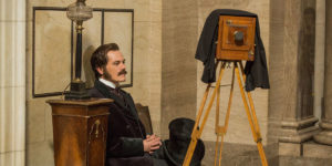 Actor Michael Shannon plays George Westinghouse. He is sitting in a black suit looking at a Victorian aged camera.