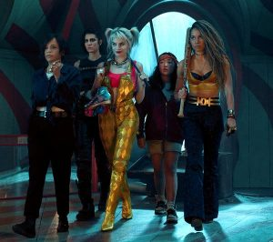 The cast of Birds of Prey standing together in a darkened room, backlit by an arching window.