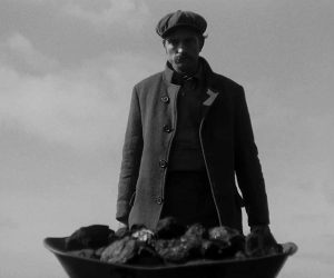A black and white picture of a man pushing a wheelbarrow filled with coal. He's dressed in wool seamen clothes with cap.