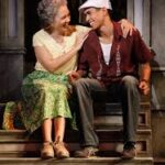 A picture of Abuela and Usnavi sitting on the stoop of their apartment in the Bronx.