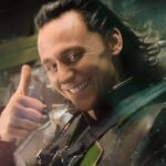 A close up picture of Loki with his long dark hair and cheeky smile, giving us the thumbs up.