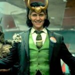 A picture of Loki in a green three piece suit and gold horns.