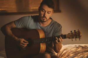 A picture of actor Michael Dorman playing the guitar.