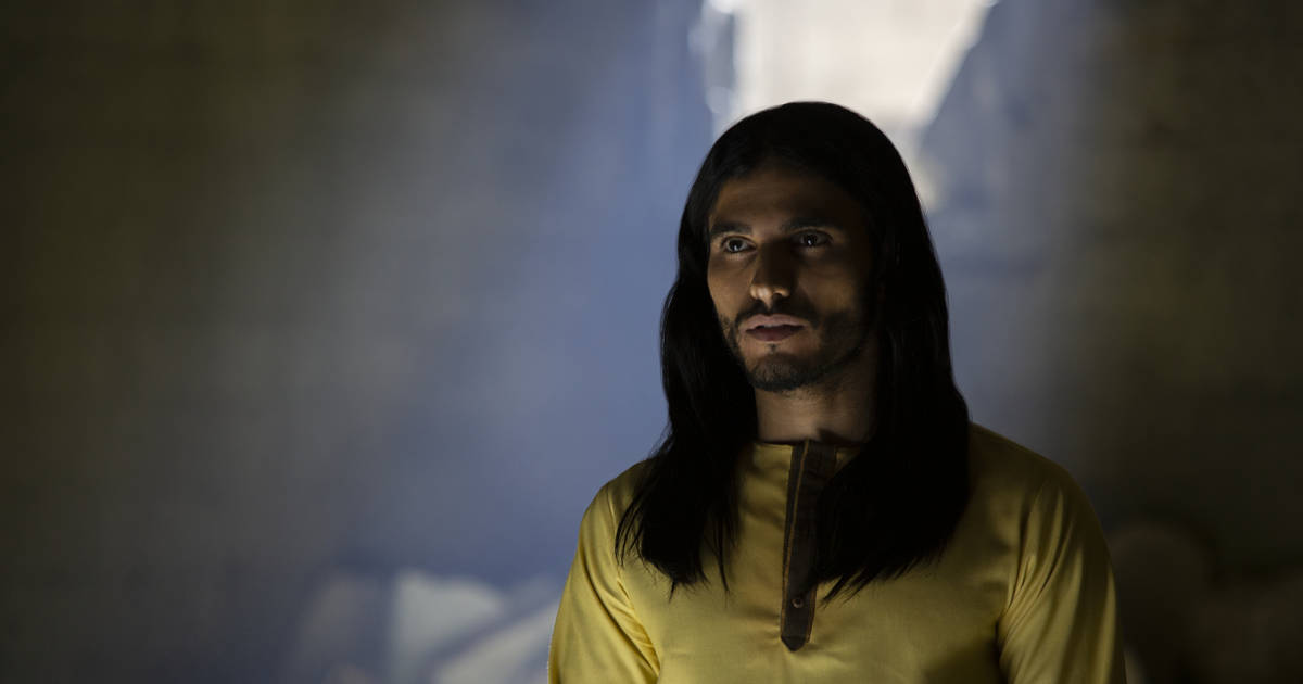 A medium shot of the actor playing the Messiah in a darkened room with filtered light surrounding his black, long hair. He is wearing a yellow tunic and his features are angelic.